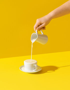 Pouring milk in a cup, on yellow background. Milk overflow from a cup