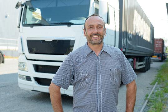 man posing in front of cargo truck
