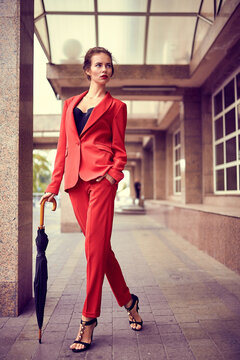Businesswoman walking near office, girl walk with umbrella while it is raining outdoors, female manager near modern bank building.