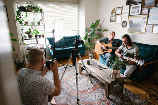 Couple playing guitars with video camera