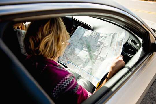 Woman looking at map inside car