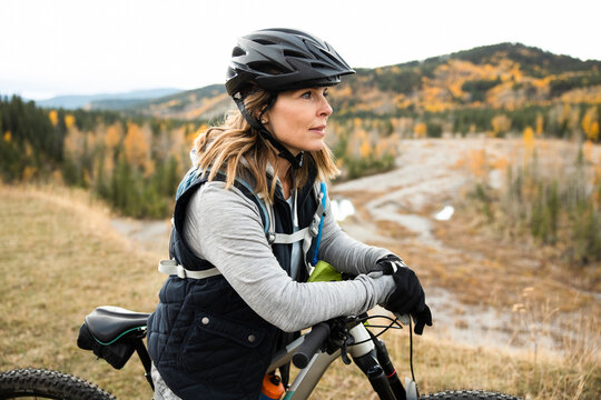 Woman leaning on bike in countryside