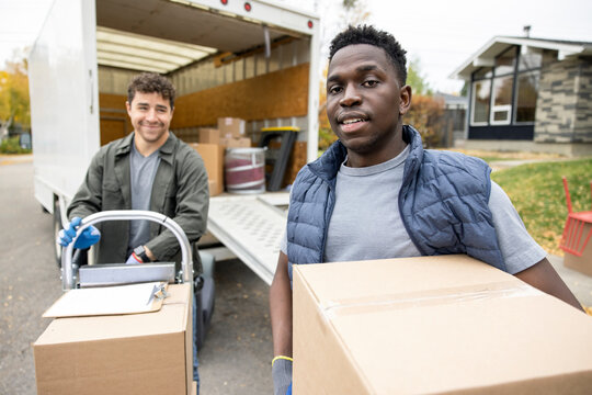 Portrait confident male movers unloading boxes from moving van