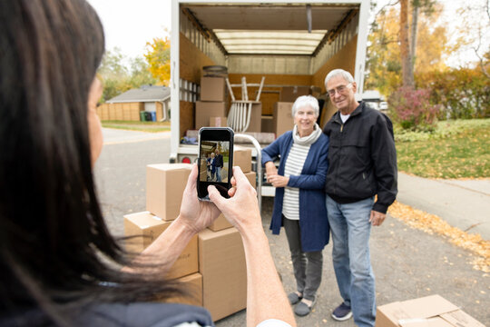 Daughter photographing senior parents at back of moving van