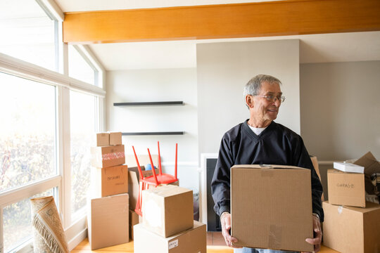 Senior man moving cardboard boxes in new home