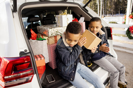 Twin brothers looking at Christmas gifts in trunk of car