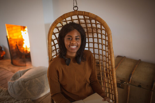 Portrait happy young woman reading book in hanging rattan chair