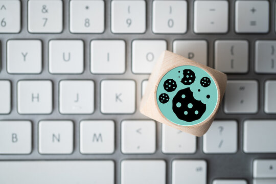 Dice with Cookie icons on a laptop keyboard conceptual of the GDPR regulations introduced by the EU governing data collection and privacy of information for individuals online.