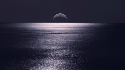 A moon just over the horizon and bright moonlight reflected in a calm sea