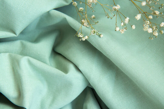 Draped beautiful folds of green natural fabric background with shadows and white Gypsophila flowers. Close up