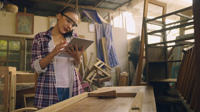 Confident woman working as carpenter in her own woodshop. She talk a telephone and using a tablet pc and writes notes while being in her workspace. Small business concept.