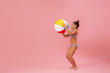 child girl in swimwear playing with beach ball on pink background. summer time