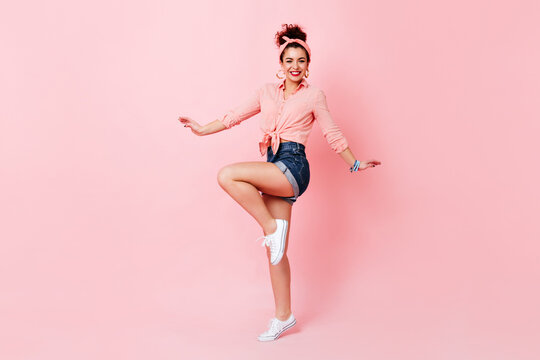Adorable young woman in shorts, cotton blouse and headband happily jumping on pink background