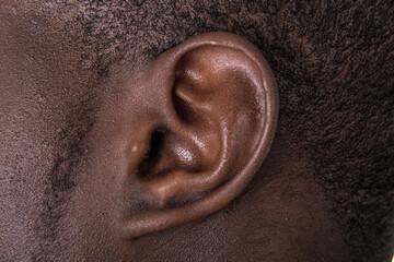 Fototapeta Black man ear close up. African american ear lobe. Hear and listen concept. obraz