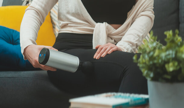 Woman massaging leg with massage percussion device at home.