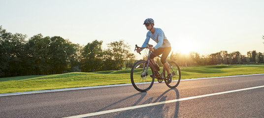 Full length shot of professional male racer in sportswear and helmet training, riding road bike on a cycle path in the park at sunset