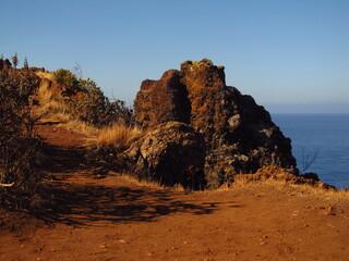 Ścieżka przy skalistym wybrzeżu na tle oceanu, wypalona ziemia i kamień na drodze, Madera, Portugalia - fototapety na wymiar