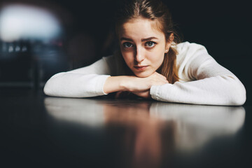 Fototapeta Young thoughtful woman resting head on hands at table