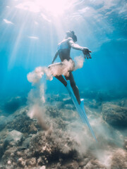 Woman glides with sand in hand. Free diver with fins posing underwater