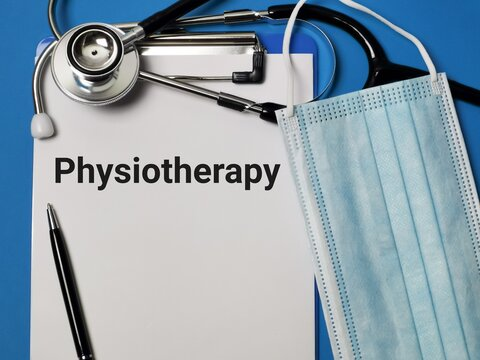 Phrase PHYSIOTHERAPY written on paper clipboard with stethoscope and medical face mask. Medical and health concept.
