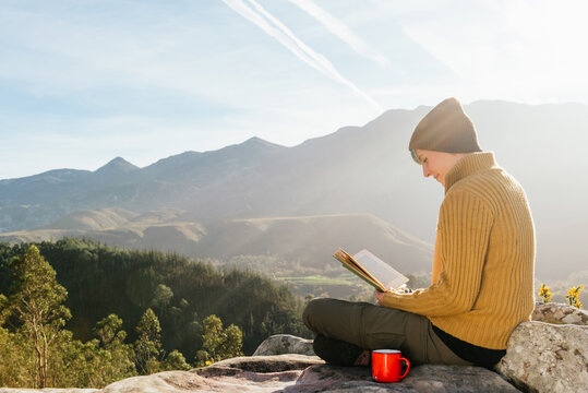 Side view of content female traveler sitting with cup of hot drink and reading interesting book on background of spectacular mountainous landscape on sunny day
