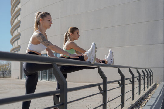 Side view of determined young slim women in sportswear doing stretching exercise for legs while standing near metal railing during outdoor fitness workout in city