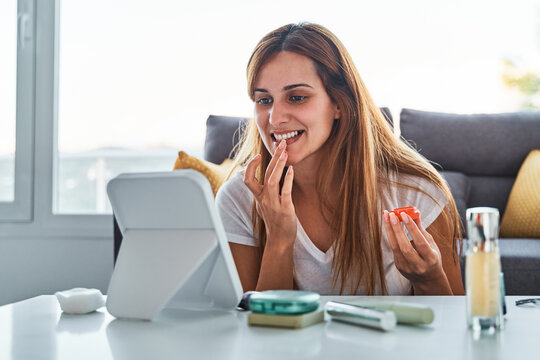 Positive young female looking at mirror and applying lip balm with finger during morning makeup session at home