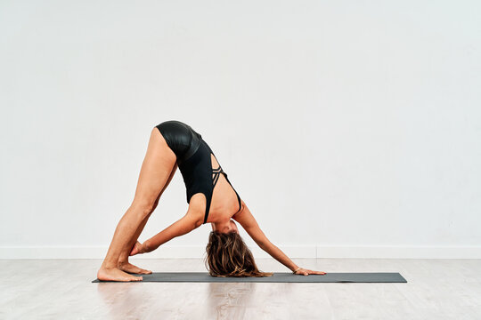 Side view of young female in sportswear doing yoga in gym on white background