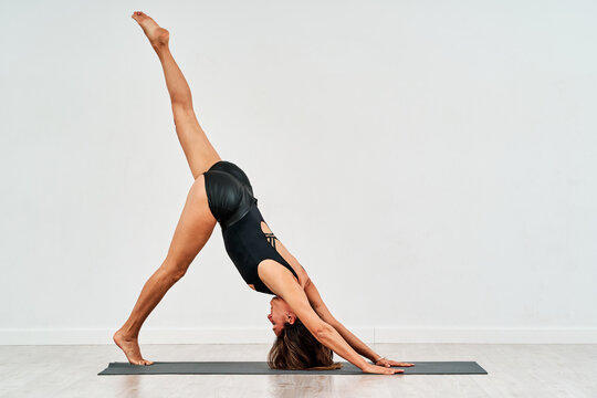 Side view of young female in sportswear showing Three Legged Downward Facing Dog pose in gym on white background