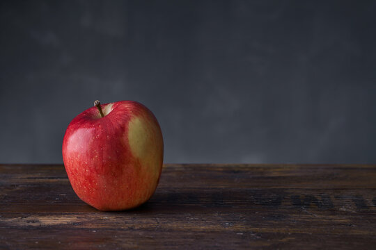 Still life with whole fresh ripe juicy red apple placed on wooden table against gray wall