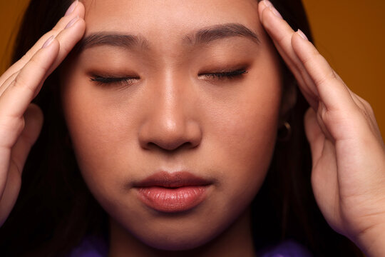 Worried chinese young woman with eyes closed over yellow background
