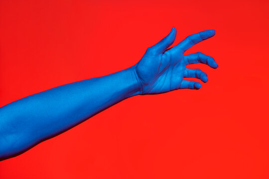 Woman's blue arm with open palm over red background. Isolated horizontal photo