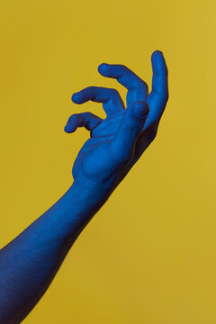 Man's blue hand holding something invisible over yellow background. Isolated vertical photo