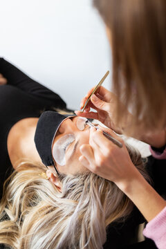 Crop professional female master with tweezer applying artificial eyelashes on young female client in face mask in light modern salon