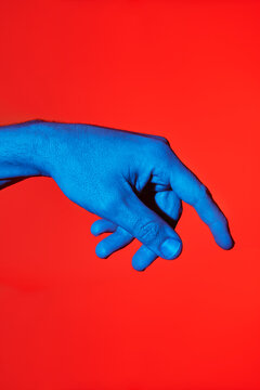 Man's blue finger pointing downwards over red background. Isolated vertical photo