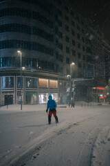 Anonymous male athlete in sportswear skiing on snowy road against building in evening during snowfall in Madrid Spain