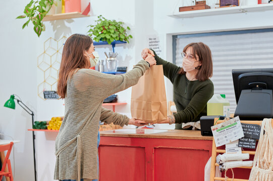 Woman in protective mask giving paper shopping bag to client while working at counter in bulk shop