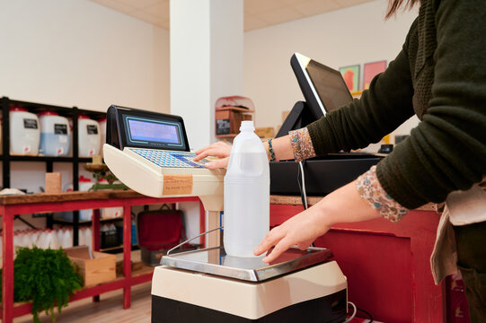Side view of crop faceless cashier weighing bottle of environmentally friendly bottle of detergent and pressing buttons on scales in shop