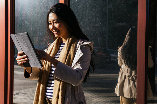 Cheerful Asian female standing against reflecting mirrored wall and browsing gadget on sidewalk in sunny day