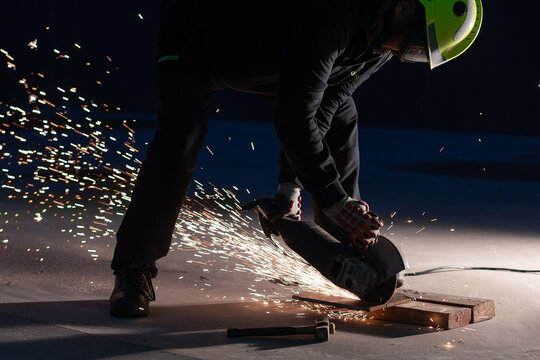 Unrecognizable male welder in protective helmet and goggles cutting iron details with chop saw during work at industrial factory at night