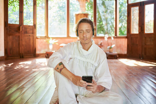 Young mindful male in white outfit with cellphone sitting on pillow while listening to yoga course with closed eyes from headset