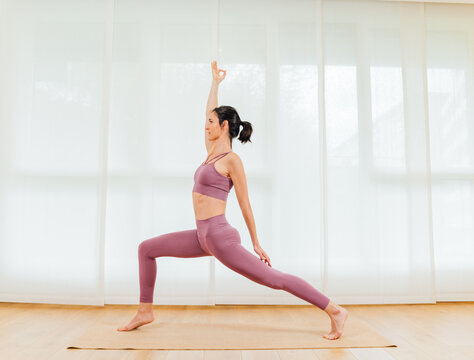 Side view full body of graceful barefoot female with hand raised practicing High Crescent asana for stretching legs