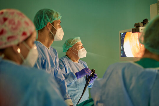 Group of anonymous doctors in surgical gowns and masks looking at monitor while examining patient with endoscope before operation in modern clinic