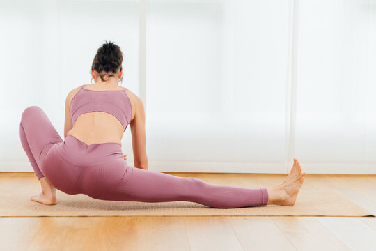 Back view full body of unrecognizable barefoot sportswoman warming up body and stretching leg before yoga training