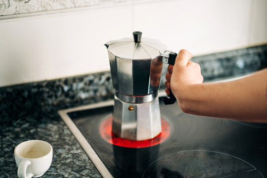 Crop person holding metal stove top coffee maker with plastic handle on modern hot hob in house kitchen in daylight