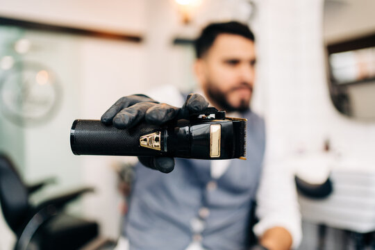 Masculine male hairdresser in glove demonstrating professional electric clipper in barbershop on blurred background