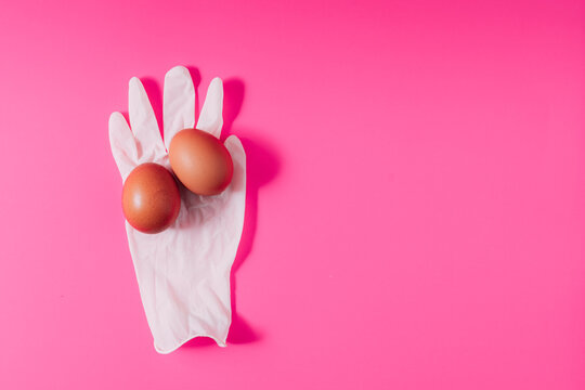 From above of similar chicken eggs on white latex glove representing organic product concept