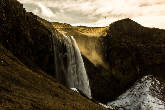 Amazing view of powerful waterfall in rocky highland terrain on sunny day in Iceland