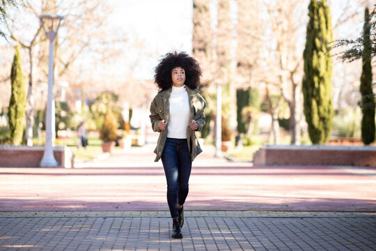 Full body of trendy young African American lady with curly hair in casual outfit walking in city park and looking away thoughtfully