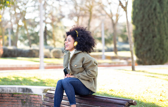 Excited young African American female millennial with curly hair in stylish outfit resting on bench in park and listening favorite song in headphones